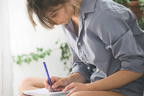 Young woman writing in notebook.