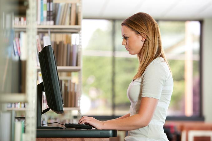 Adult student working on computer in the library